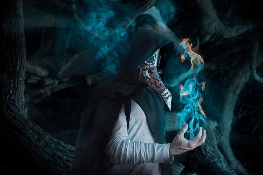 A fine art composite photo with a person wearing a black cape and plague doctor mask. He is holding blue and orange flames in his right hand.