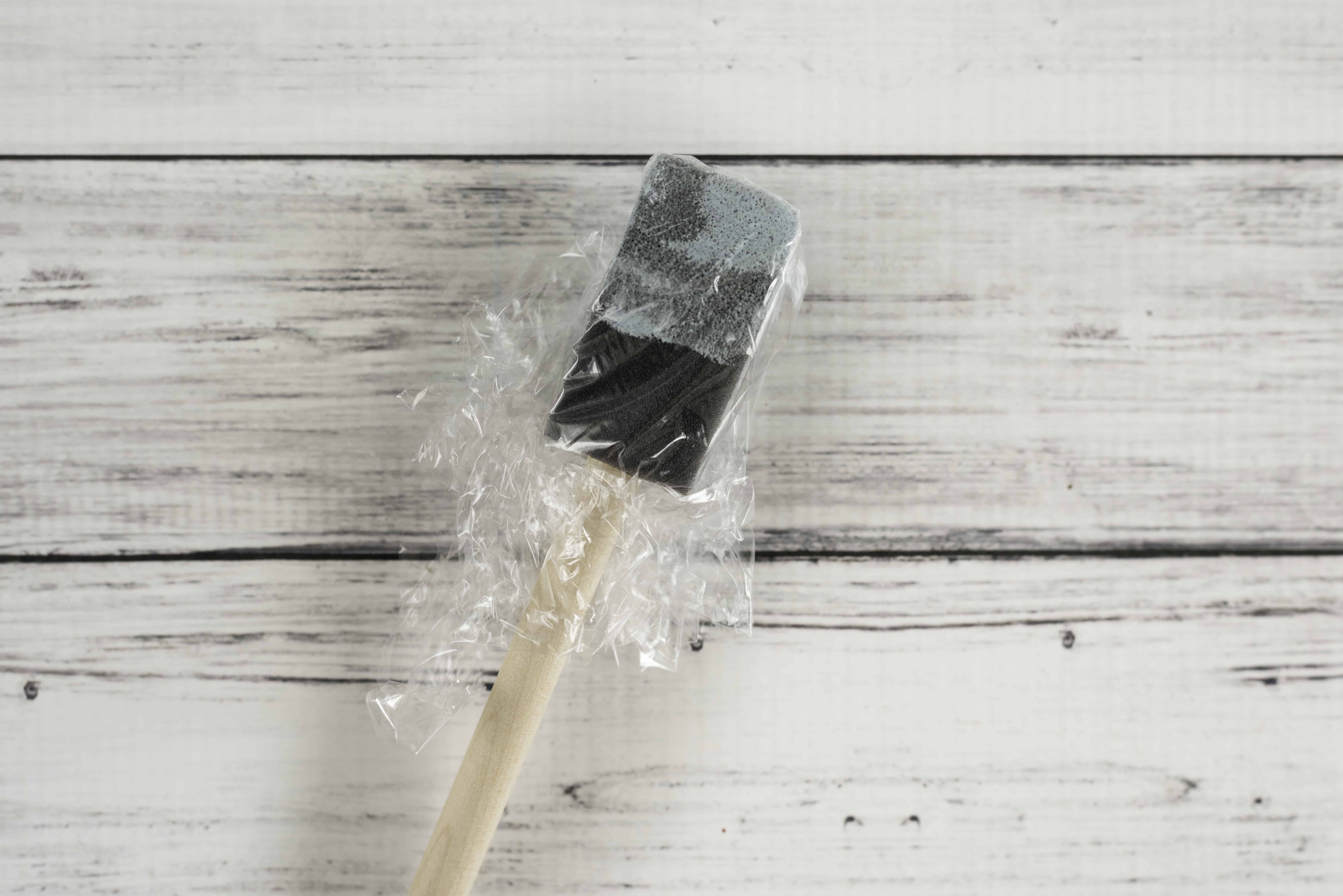 cover the paintbrush with plastic wrap
