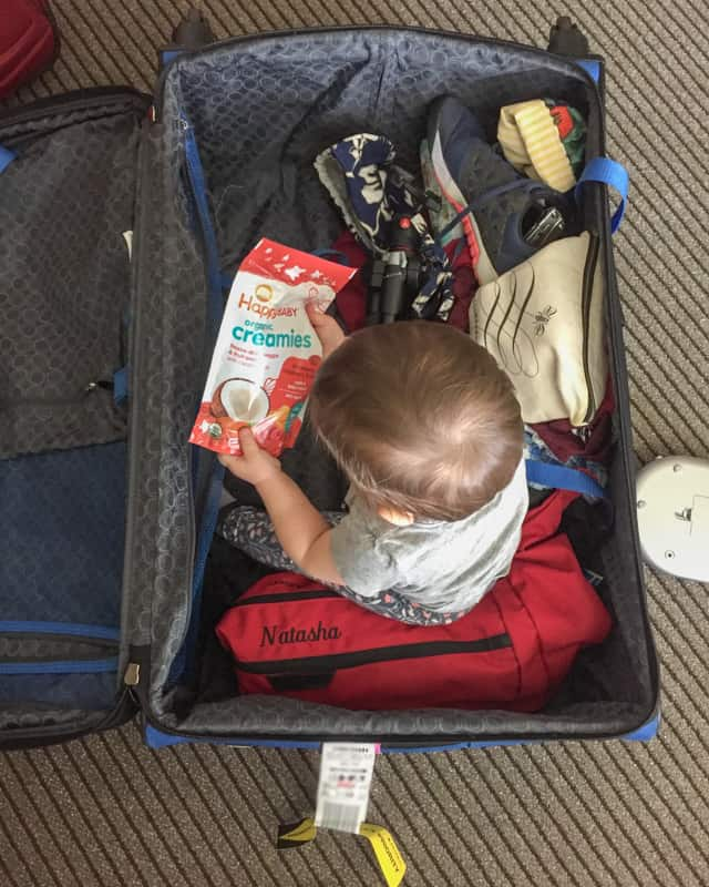 baby sitting in luggage playing with food