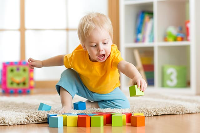 a boy toddler playing with wood blocks on the floor. He is sitting on a tan rug. White shelves with colorful toys are visible in the background.