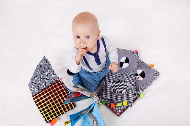 baby sitting in a pile of chewable cloth books