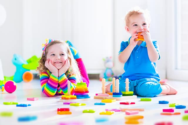 older toddlers playing with wood toys