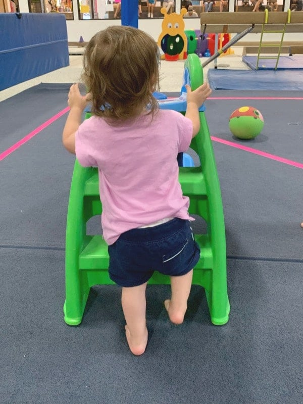 A toddler in a pink shirt climbing a small green and blue plastic slide