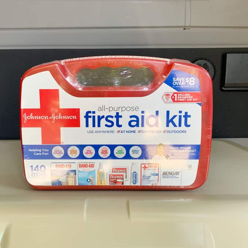 red first aid kit on top of an ice chest