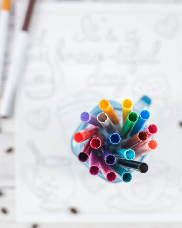 A top down view of a jar of Crayola super tip markers sitting on an out of focus coloring page