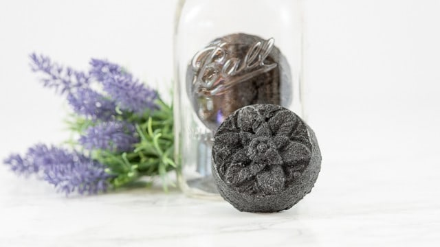black bath bomb made with activated charcoal leaning against a glass jar with lavender