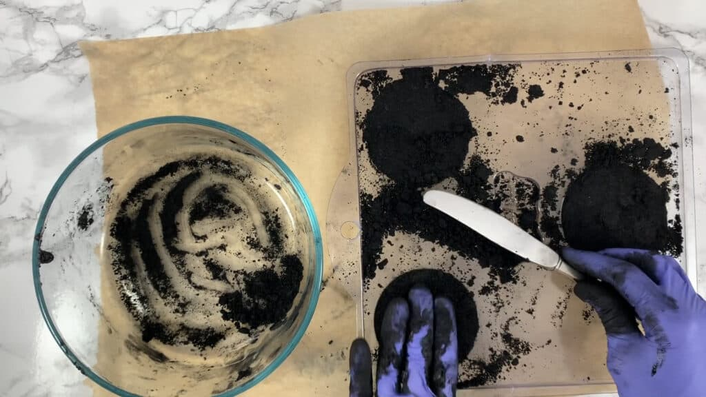 Scraping bath bomb molds with a knife to remove excess mixture