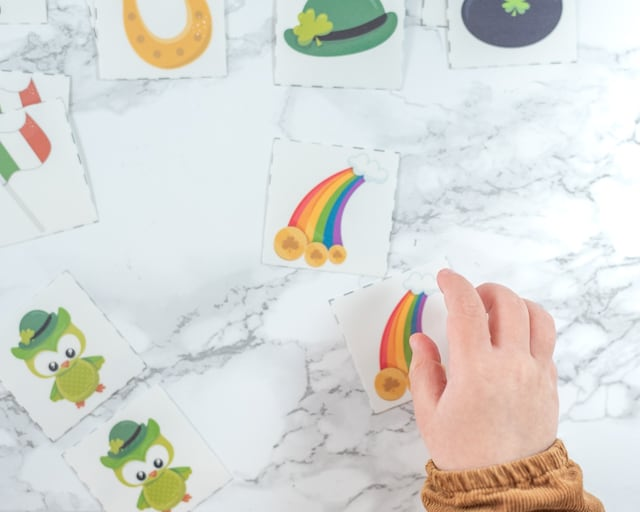 a toddler's hand reaching for a matching card with a rainbow on it. A set of St. Patrick's Day matching cards for toddlers is in the background on a white marble backdrop.