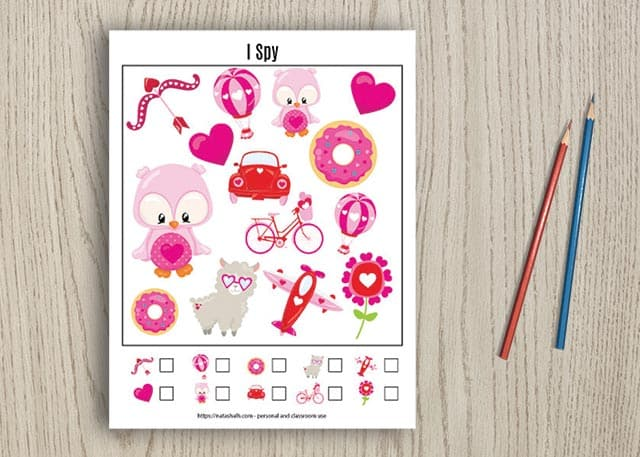 Free printable Valentine's Day I spy game for young children on a wood background with two pencils