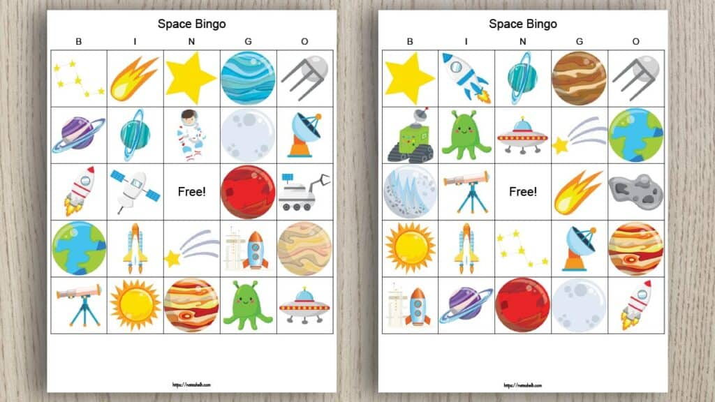 Two free printable space bingo boards on a wood background. The bingo cards feature cartoon space-themed images like planets, stars, satellites, and telescopes.