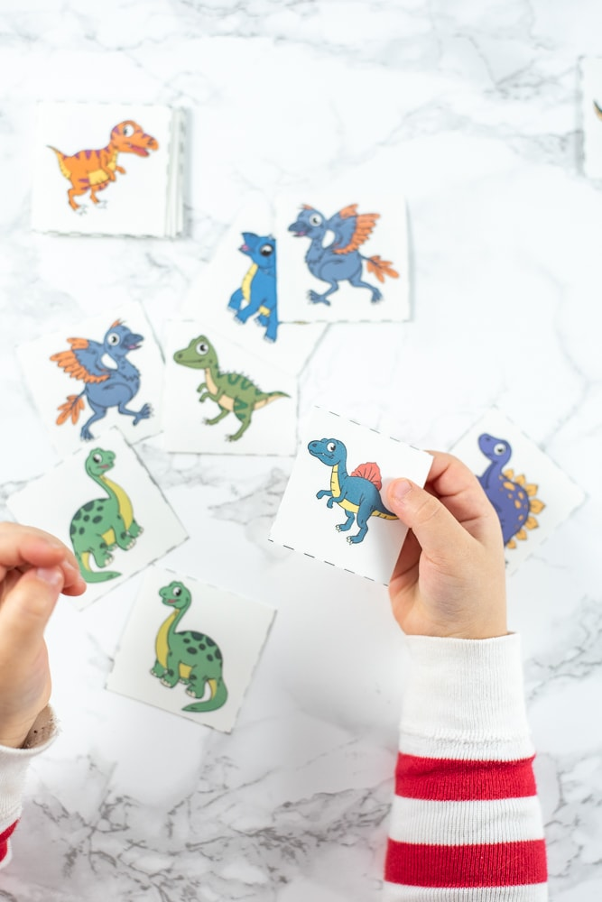 A top down image of a toddler's hands holding printable dinosaur matching cards. The toddler's hands and arms in a red and white striped shirt are visible against a white marble background. Several blue and green dinosaur matching cards are on the surface.