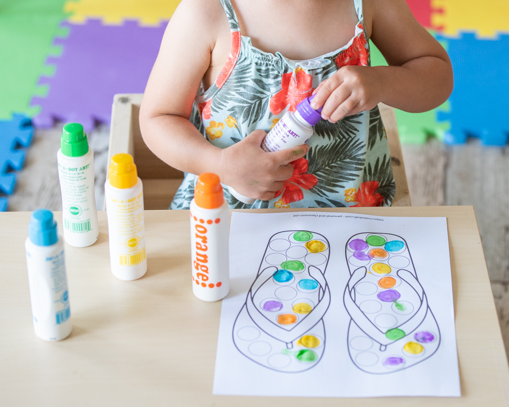 A toddler unscrewing the lid of a purple do a dot marker. Four more markers are visible on a table in front of her. Only the toddlers hands and body are visible.