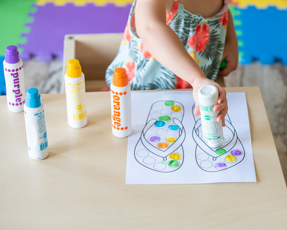 A toddler using a summer themed printable do a dot worksheet showing a sand bucket. The toddler is sitting at a table with five do a dot markers and holding the purple marker. Only the toddler's body and hands are visible. Her face is out of the frame.