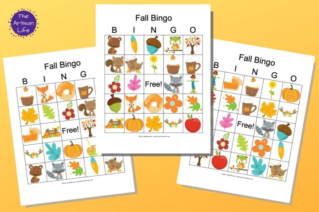 """Three free printable fall bingo cards featuring cartoon fall images. The bingo card previews are on a colorful background with a yellow to orange gradient. In the top left is a purple circle with the white text """"The Artisan Life"""""""