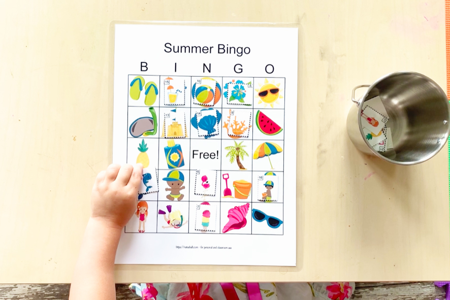 A top down shot of a toddler table with a summer picture bingo card. The toddler is matching a dolphin tile to the dolphin image on her card. Several other pictures are covered and the rest of the call cards are in a metal bucket on the table.