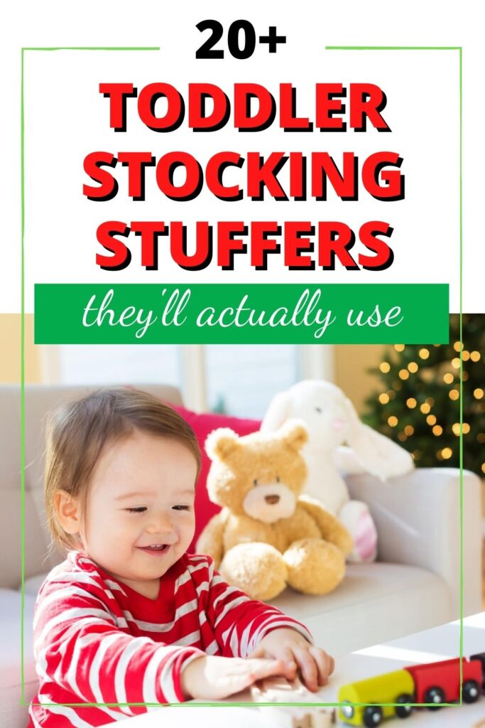 """text """"20+ toddler stocking stuffer ideas"""" above a picture of a little girl in red and white striped pajamas playing with a wood train. Stuffed animals are visible on the couch behind her and there's a Christmas tree with lights in the top right."""