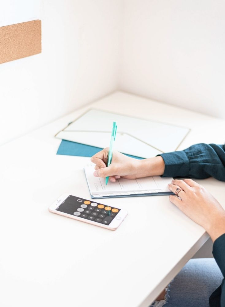 A shot of a woman's hands writing in a planner while adding doing her monthly budgeting. She is holding a green pen and using her iPhone calculator.