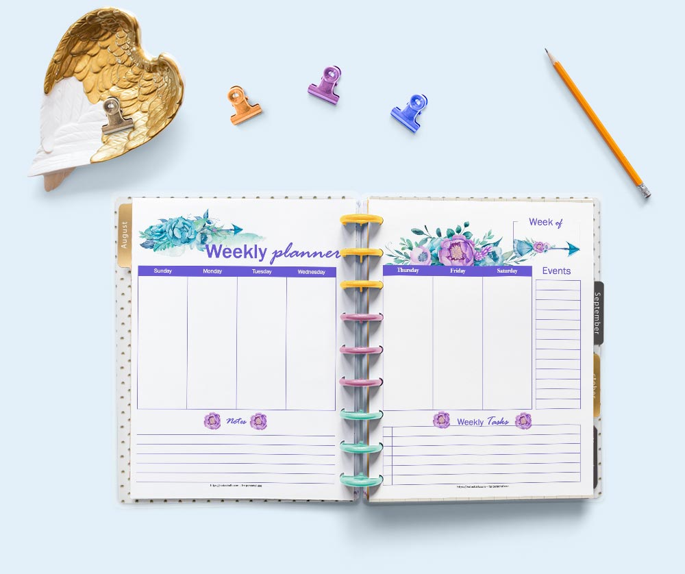 A flatly scene of a Happy Planner classic planner open to a two page spread of weekly planner pages. The pages feature purple and pink watercolor anemone flowers and boho arrows. The planner is surrounded by stationary supplies.