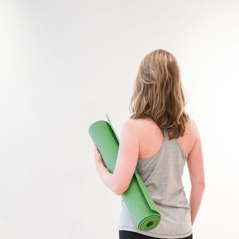 A shot of a woman from the waist up in a grey tank top holding a green yoga mat. She had shoulder length dirty blond hair and is facing a white wall