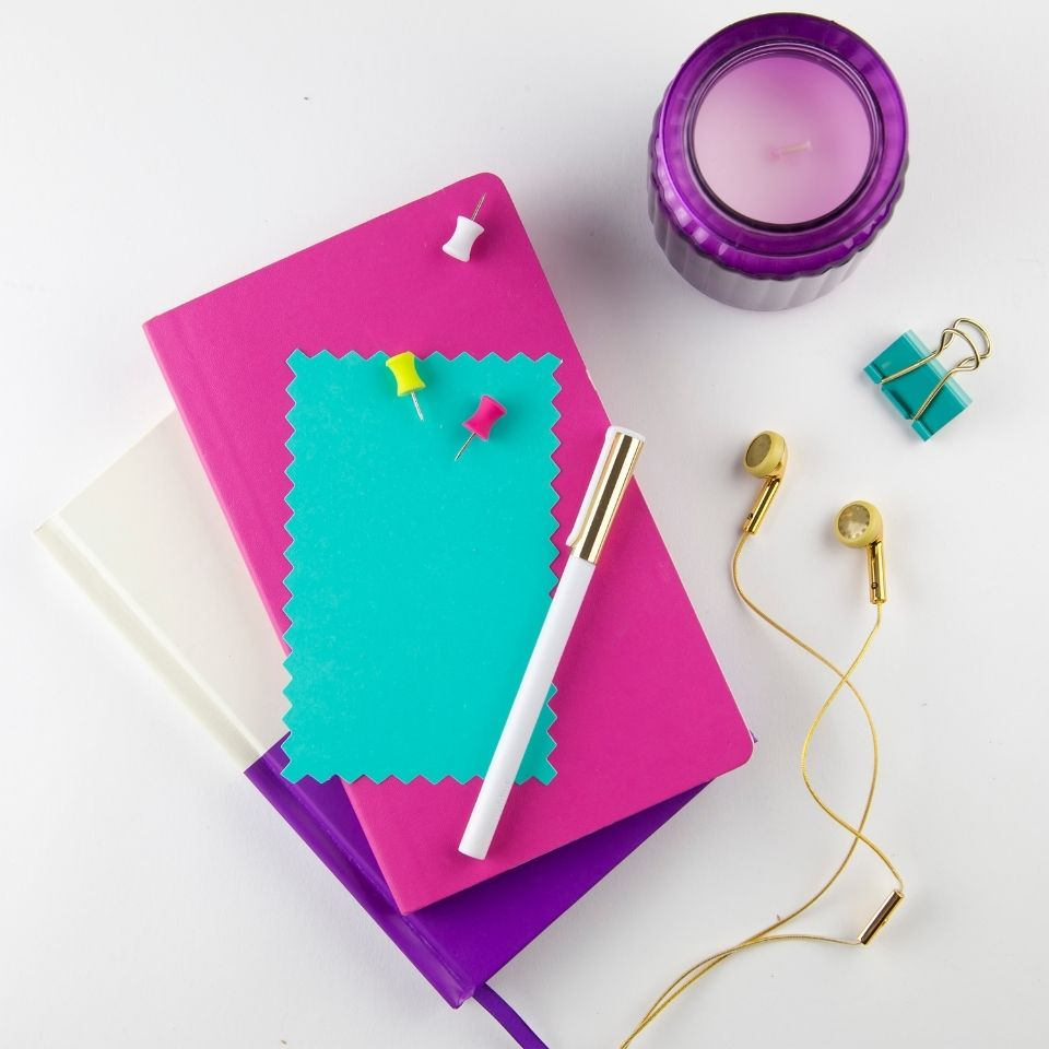 Stationary supplies on a white background. A white and purple notebook is in the middle with a pink notebook and teal notecard on top. A purple candle is above and to the right. A pair of gold earbuds is next to the notebooks.