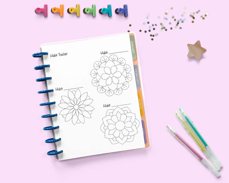 a Happy Planner open to a page with three floral habit trackers. There are gel pens, glitter, and colorful binder clips on a pink surface behind the planner