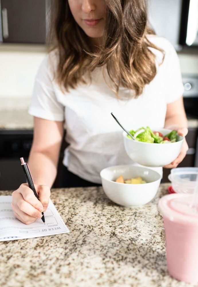 An image of a woman writing in a weekly planner on her kitchen counter while holding a bowl of salad.