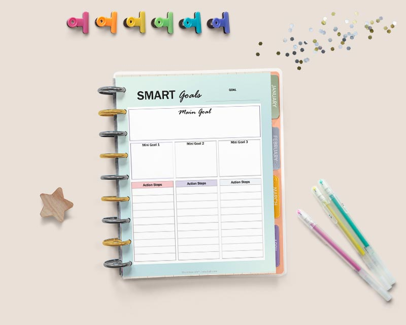 "An open Happy Planner with a page reading ""smart goals"" with spaces to break each goal into three parts with action steps. There are gel pens, glitter, a wood star, and colorful binder clips around the planner."