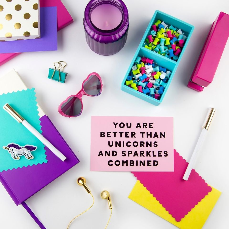 """Teal, purple, and pink stationary supplies with a pair of heart lens pink sunglasses. In the middle is a pink notecard with the message """"you are better than unicorns and sparkles combined"""""""