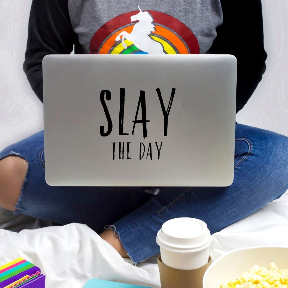 """A woman in a rainbow unicorn short working on a laptop with the words """"Slay the day"""" on the back. A cup of coffee is visible by her feet. Her face is not visible."""