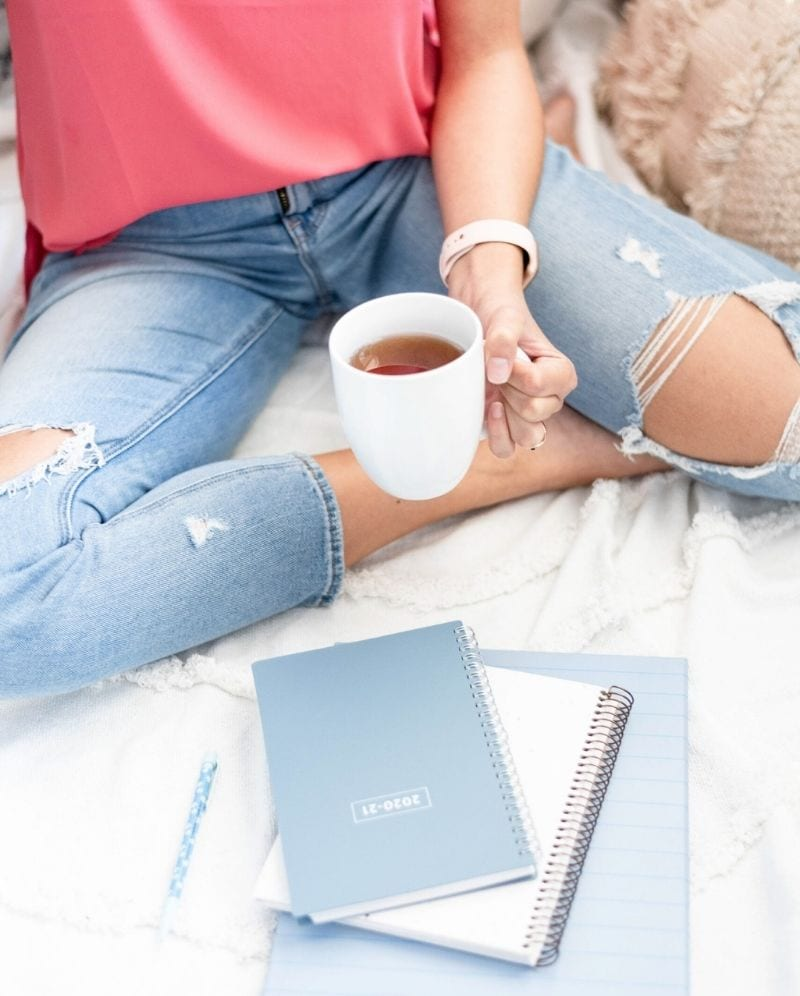 A woman with ripped knee jeans sitting on a white blanket with blue spiral notebooks and a mug of tea