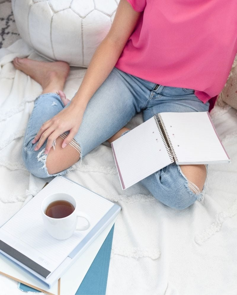 An image of a woman sitting on a bed with an open notebook on her lap. She is wearing jeans with ripped knees and has a mug of tea.