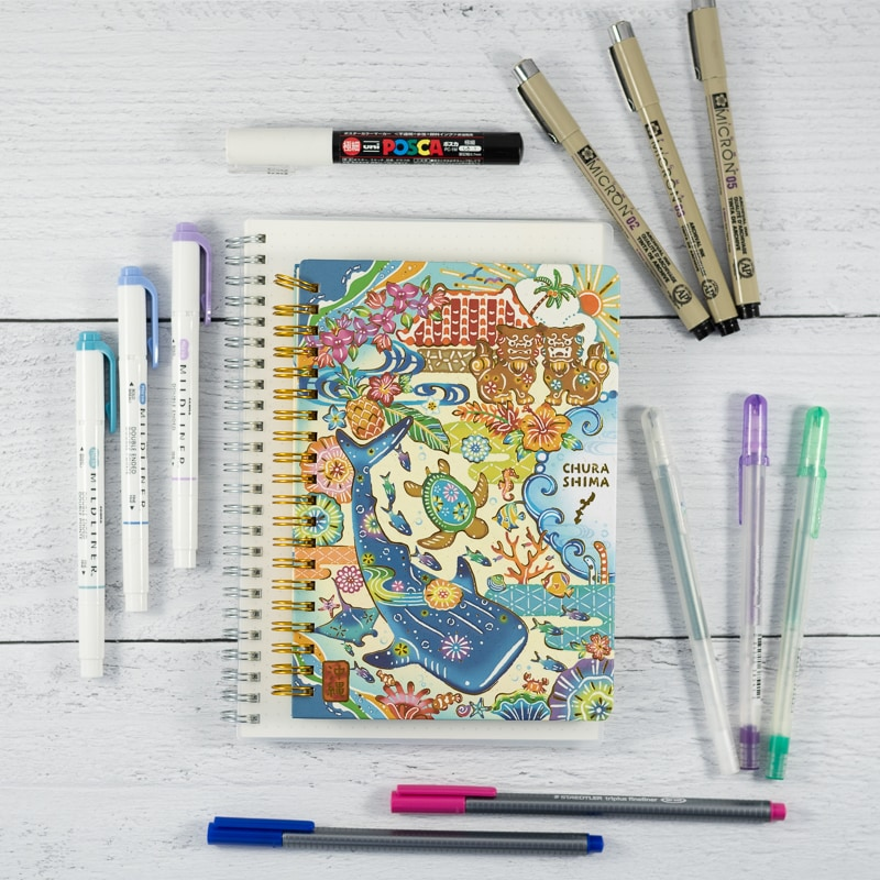 An image with a spiral Japanese notebook and a collection of bullet journal pens including Sakura Microns, gelly roll pens, Zebra midliners, and fineliner markers