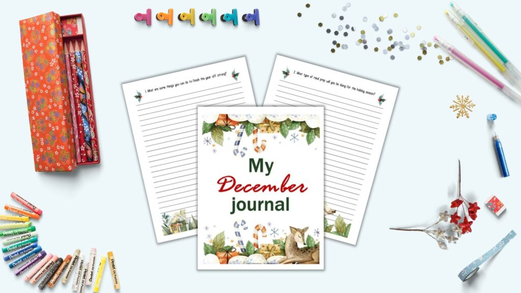 """A flatly mockup with journaling supplies and three journal pages in the center on a light blue background. The pages include """"My December Journal"""" with watercolor illustrations in the front and center. Behind are two lines pages with journal prompts at the top and a watercolor border at the bottom. Props on the surface include gel pens, glitter, blue washiest tape, and a Japanese pencil case with red flowers and pencils."""