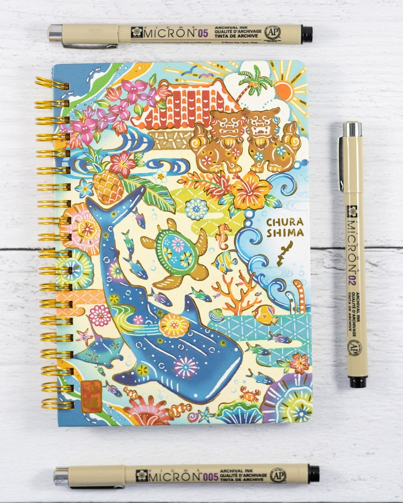 Micron pens next to a whale shark themed small spiral notebook