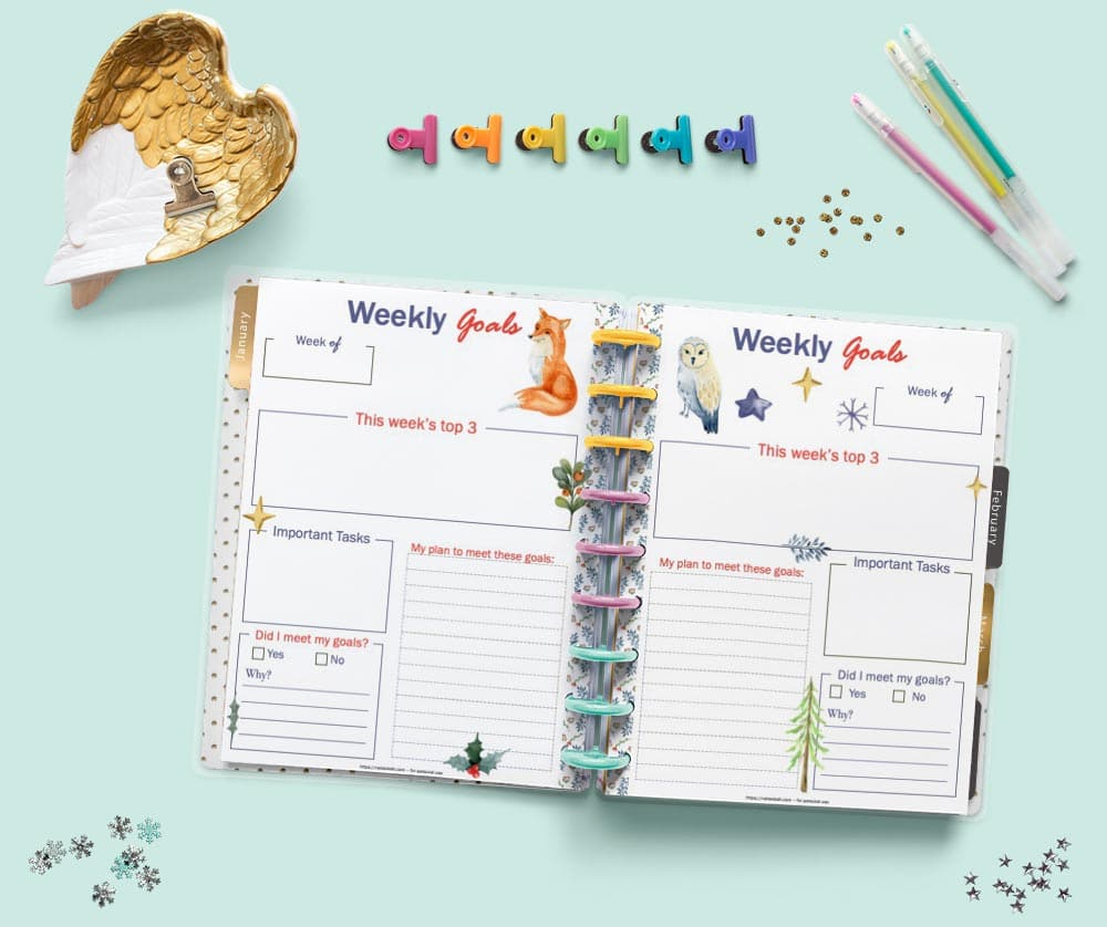 An open Happy Planner Classic disc bound planner showing a daily goals and weekly goals planner page. The pages feature watercolor illustrations with a fox, an owl, and winter greenery. There are desk supplies around the planner including colorful binder clips and three gel pens.