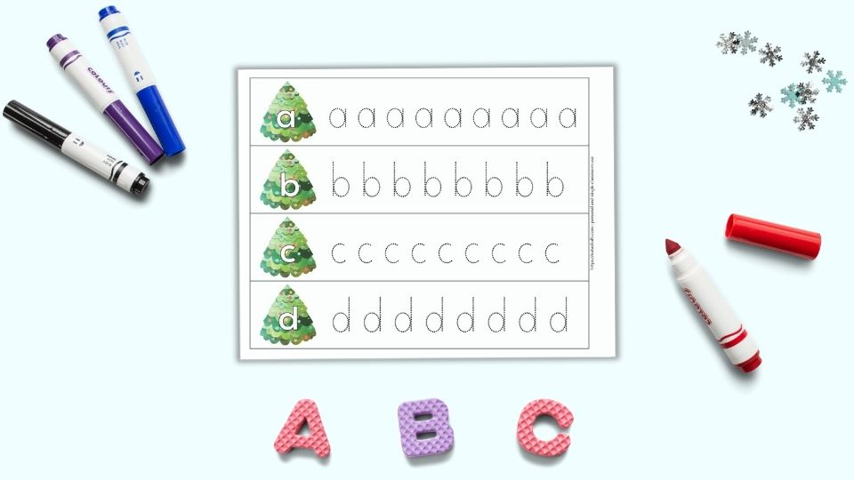 """A preview of one printable alphabet tracing page for preschoolers. The page has four rows with one letter per line - a, b, c, d"""" A large bubble letter is on a Christmas tree on the left. To the right is a line of dotted letters to trace. The pages are on a light blue surface. Below the pages are foam letters """"A B C."""" There are four colorful children's markers around the printable pages."""