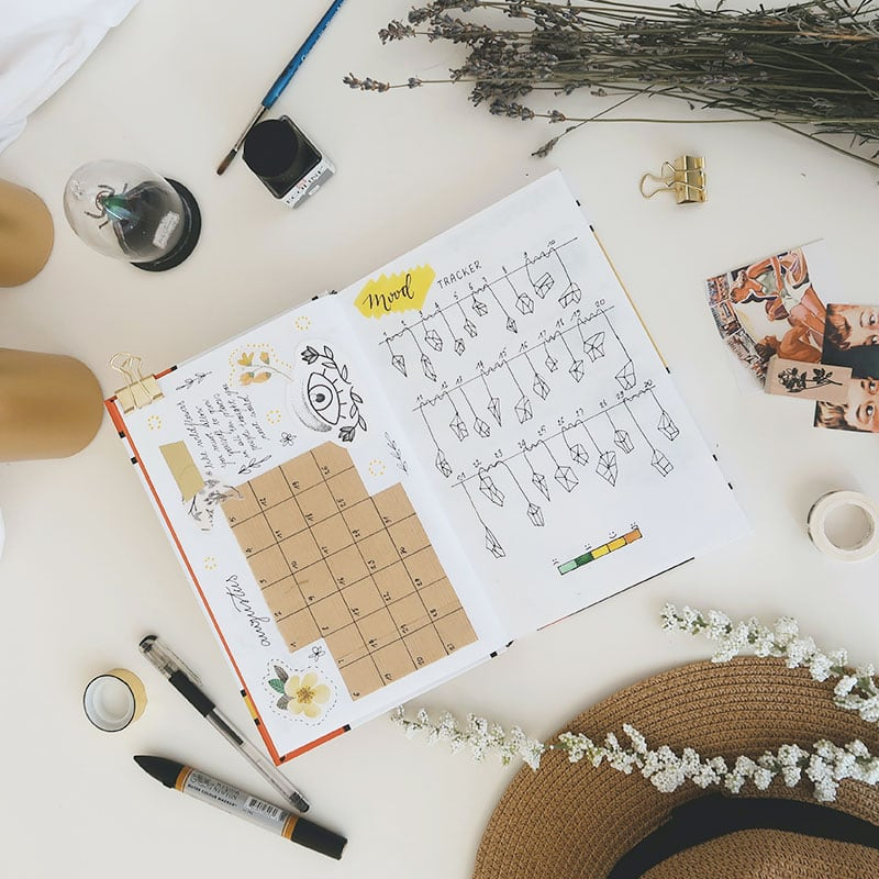 a flatly image showing an open bullet journal with a monthly layout on the left and a mood tracker on the right. The notebook is surrounded y office supplies, a sun hat, lavender, and two gold pillar candles.