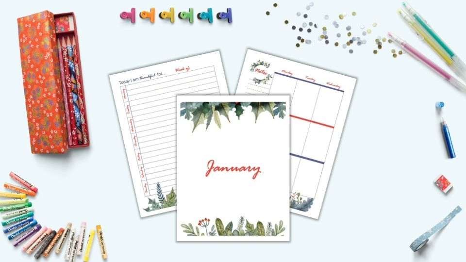 A preview of three printable January planner pages including a gratitude journal page, cover page, and first page of a vertical weekly layout. The pages are on a blue surface surrounded y desk supplies including gel pens, colorful binder clips, oil pastels, and a red pencil case.