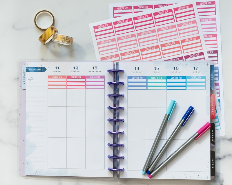 An open happy planner with three rolls of gold washi tape, three colorful pens, and two pages of printable sticker sheets. The stickers are for recording three daily gratitudes. The top row of each daily box in the open planner has a colorful gratitude sticker.
