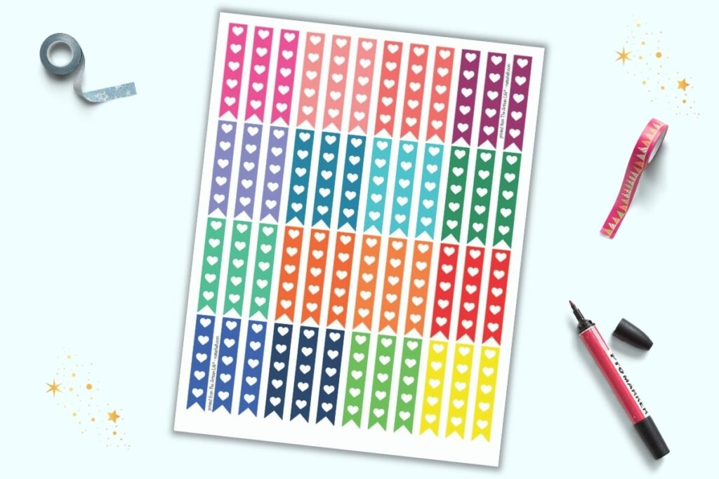 A sheet of printable stickers on a light blue background. The stickers are narrow vertical flags with 5 hearts to use as checkboxes. There are 16 different rainbow colors with three flags each per color. The sheet is on a light blue background with blue washi tape, red washi tape, and a red marker.
