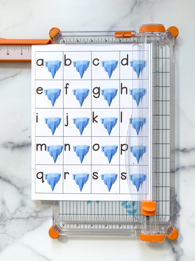 A paper trimmer trimming the right margin off a page with 20 tiles. Each tile as a lowercase letter a-t and an iceberg.