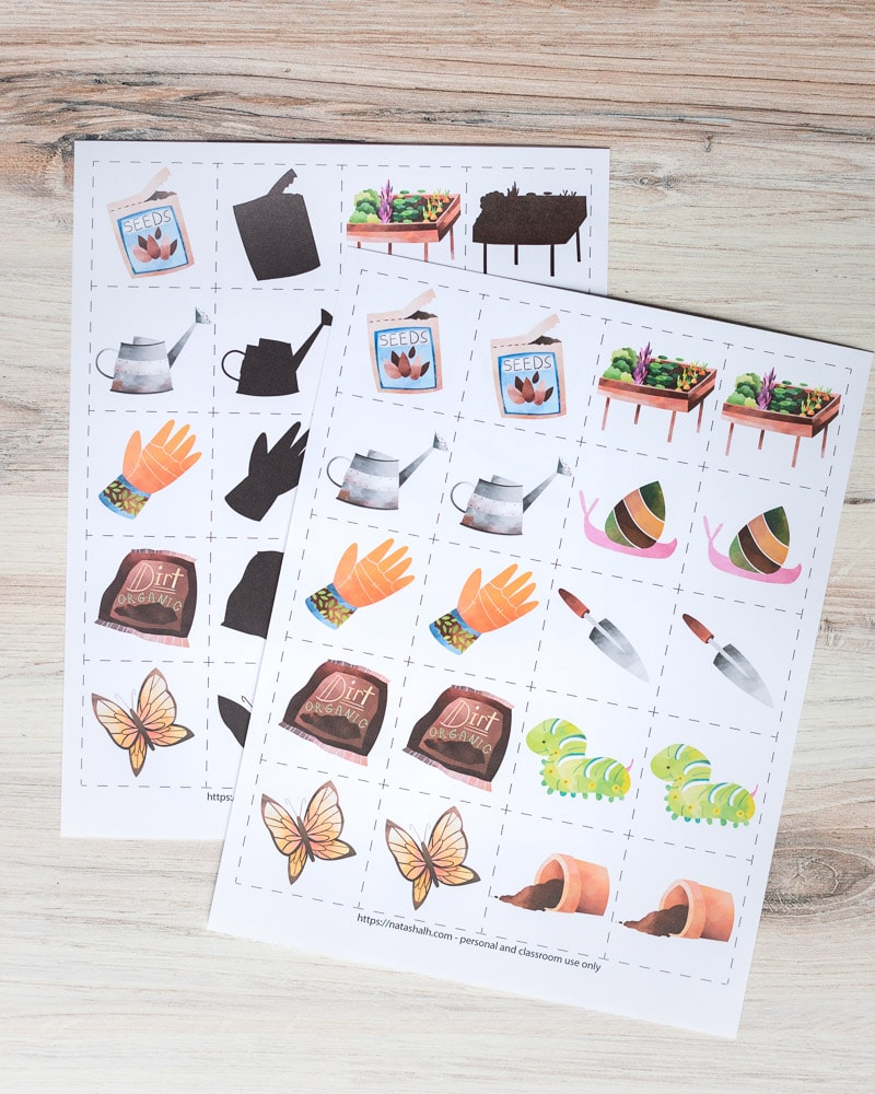 """A preview of two free printable garden matching game pages. Each page has pairs of 10 garden related images inside dotted squares to cut out and use as a matching card game. The page in back has half of the images in color and the other half """"blacked out"""" for a shadow matching game. The two printables are on a wood surface."""