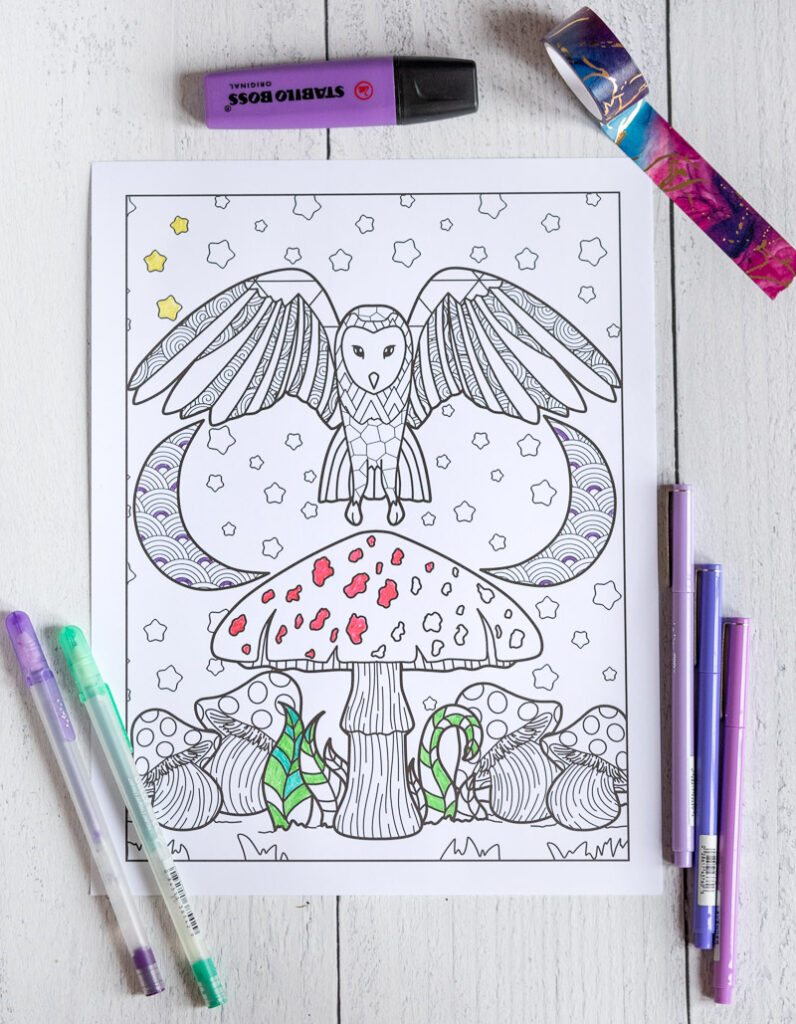 A printed owl coloring page with an owl over a mushroom with two crescent moons in the background. The page is partially colored and on a white wood surface with purple pens, a purple highlighter, and purple and blue washi tape