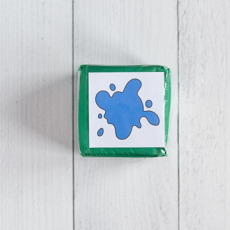 A green gross motor cube with an insert showing a blue paint splash.