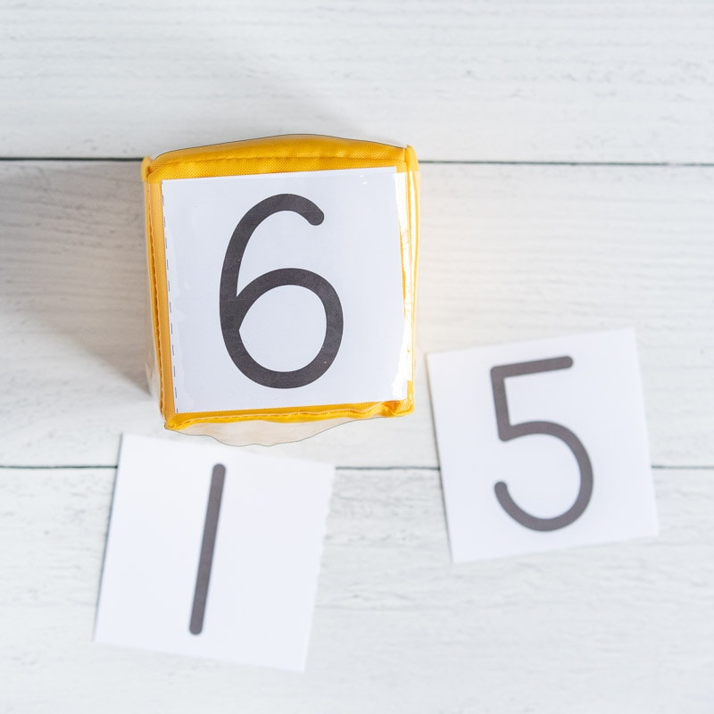 A yellow gross motor/differentiated instruction cube with the numeral 6 showing. Cut out cards with 1 and 5 are visible on the white wood surface under the die.