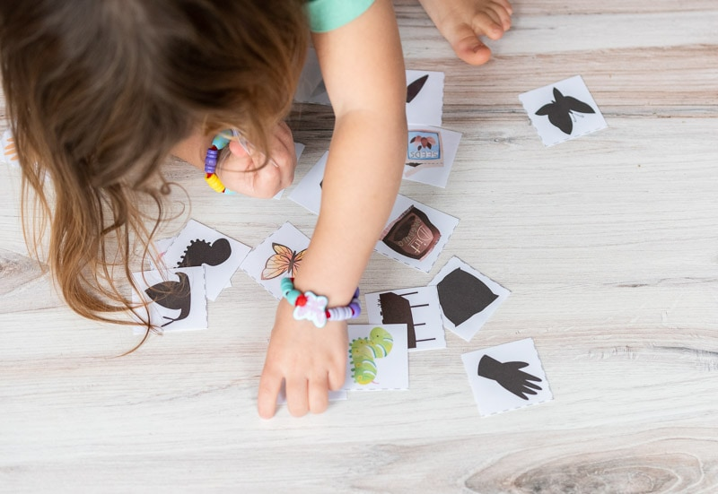 A top down view of a young girl wearing butterfly bracelets playing with shadow matching cards on a wood floor.