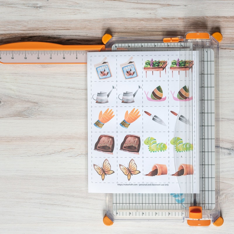 A paper trimmer on a wood surface. A printed page of garden matching cards is resting on top of the paper trimmer.