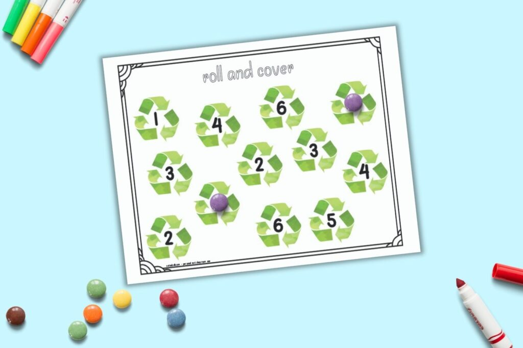 A printable roll and cover mat for preschool math. The page has the numbers 1-6 two times apiece. Each number is in the center of a recycling symbol. Purple round candies cover two of the numbers and an additional pile of candies is on the bottom left of the image.