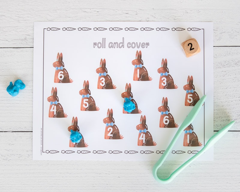 A printable Easter roll and cover mat with 12 chocolate bunny images. Each bunny clipart has a number 1-6. Two numbers are covered with small blue dinosaurs. A pair of seafoam colored plastic tongs is on the bottom right of the page.