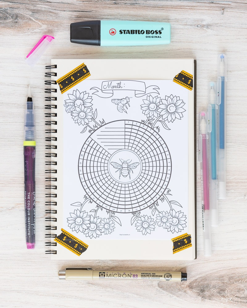 A notebook with a bee themed circular habit tracker taped to the page with washi tape. There are desk supplies around the notebook, including a brush pen, Sakura Micron pen, Stabilo highlighter, and Gelly roll pens.